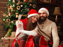 Happy Christmas couple in New Year decorations at home Stock Photos