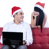 Happy christmas couple shopping online. Happy christmas couple using laptop to christmas shopping online, isolated on white Stock Images