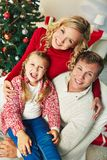 Happy Christmas eve. Portrait of happy family of three looking at camera on Christmas day Royalty Free Stock Images