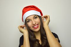 Happy Christmas face. Attractive young woman puts her Santa Claus hat on gray background. Happy Christmas face. Attractive young woman puts her Santa Claus hat Royalty Free Stock Photography