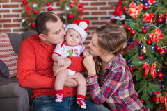 Happy Christmas Family portrait. Smiling Parents with baby daughter at Home Celebrating New Year. Christmas Tree Royalty Free Stock Photography