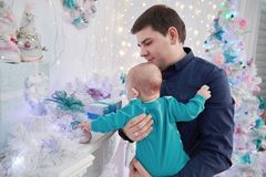 Happy Christmas. father shows his baby Christmas gifts. The concept of fatherhood stock images