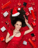 Happy Christmas Girl Holding Candy Cane surrounded by Presents. Beautiful smiling woman in sweet Christmas fantasy portrait with lollipop and gifts Stock Photo
