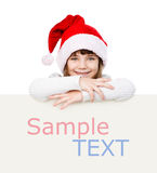 Happy Christmas girl with santa hat behind white board.  Stock Photos