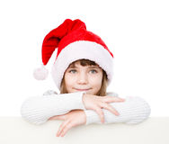 Happy Christmas girl with santa hat behind white board. isolated. On white background stock images