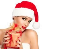 Happy Christmas Girl in Santa Hat hold a Gift in Hands Royalty Free Stock Photos