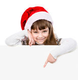 Happy Christmas girl with santa hat points down. isolated on white Stock Photo