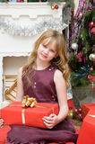 Happy Christmas. Happy girl with gifts by the fireplace Stock Image