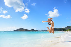 Happy Christmas hat girl jumping of joy on beach. Happy Santa hat girl jumping of joy and fun on Christmas holiday travel in Caribbean beach destination. Winter stock photos