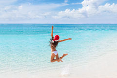 Happy Christmas hat girl jumping of joy on beach. Happy Santa hat girl jumping of joy and fun on Christmas holiday travel in tropical beach destination. Winter royalty free stock images