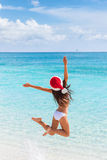 Happy Christmas hat girl jumping of joy on beach. Happy Santa hat girl jumping of joy and fun on Christmas holiday travel in tropical beach destination. Winter stock image