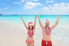 Happy Christmas holiday - couple on Hawaii beach. Happy Christmas holiday - multiracial joyful couple cheering arms up on Hawaii beach for their winter vacation Stock Photography
