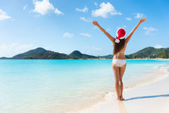 Happy Christmas holiday woman on beach vacation. Winning arms up in success royalty free stock photo