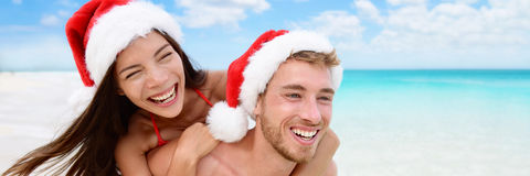 Happy Christmas holiday woman and man couple banner. Happy Christmas holiday women and men couple in Santa hat laughing on beach vacation having fun. Asian Stock Image