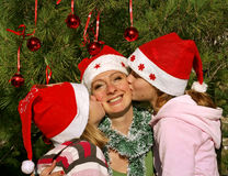 Happy Christmas holidays. Children (girls) kiss his happy smiling mother on the cheek (face), congratulate the Christmas holidays Stock Photos