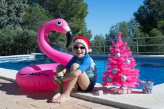 Happy Christmas Holidays. A cute child wearing a Santa hat by the swimming pool with a pink xmas tree and a flamingo buoy. Merry Christmas Postcard Design royalty free stock photography