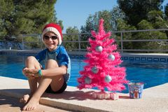 Happy Christmas Holidays. A cute child wearing a Santa hat by the swimming pool with a pink xmas tree. Merry Christmas Postcard royalty free stock photography