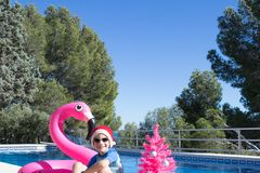 Happy Christmas Holidays in warm countries. A cute child wearing a Santa hat by the swimming pool with a pink xmas tree. And a flamingo buoy. Merry Christmas stock image