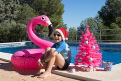 Happy Christmas Holidays in warm countries postcard design. Happy Christmas Holidays. A cute child wearing a Santa hat by the swimming pool with a pink xmas tree royalty free stock photos