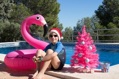 Happy Christmas Holidays in warm countries postcard design. Happy Christmas Holidays. A cute child wearing a Santa hat by the swimming pool with a pink xmas tree stock image