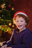 Happy Christmas kid. Cute little boy (6) wearing a christmas hat and sitting before the christmas tree Stock Images