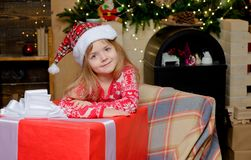 Happy Christmas little girl is looking at the camera with a big Christmas present. Beautiful little girl wearing Santa stock photo