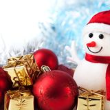 Happy Christmas, New Year, snowman, gifts in golden boxes and red balls on a blue and white bokeh background. royalty free stock image