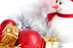 Happy Christmas, New Year, snowman, gifts in golden boxes and red balls on a blue and white bokeh background. royalty free stock photography