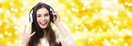 Happy christmas party concept woman listens to music with headphones doing a rock and roll symbol on blurred golden lights stock images