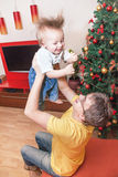 Happy Christmas!. Portrait of father and son near christmas tree. Happy dad is holding cute baby boy. Man and (child) kid are smiling, having fun and enjoying Royalty Free Stock Photography