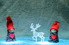 Happy Christmas puppets with reindeer. Scenery of two happy christmas puppets with big red caps and hearts  standing next to white reindeer Royalty Free Stock Photos
