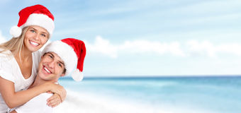Happy christmas santa couple on the beach. Royalty Free Stock Photos