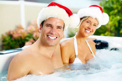 Happy Christmas santa couple in jacuzzi. royalty free stock photography