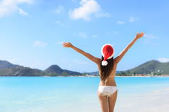 Happy Christmas santa hat woman on beach vacation. Happy Christmas holiday santa hat woman on beach vacation winning arms up in success stock image