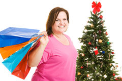 Happy Christmas Shopper. Happy plus sized model holding shopping bags, standing in front of a Christmas tree.  Isolated on white Stock Photography