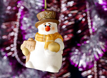 Happy Christmas snowman, tinsel as background. Royalty Free Stock Photo