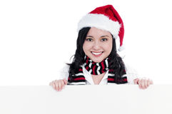 Happy Christmas Woman Holding Blank Billboard. Portrait of a beautiful young Christmas woman holding blank sign, isolated on white Royalty Free Stock Image