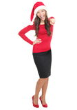 Happy Christmas woman pointing. Pointing Santa girl happy for christmas and excited pointing at camera standing in full length isolated on white background Stock Photos