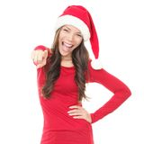 Happy christmas woman pointing. Woman in santa hat excited for Christmas. Surprised asian beautiful happy girl pointing at camera isolated on white background Royalty Free Stock Image