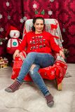 Happy woman sitting on chair with Christmas tree royalty free stock image