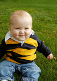 Happy Chubby Baby. Cute chubby baby laughing and sitting in the grass royalty free stock images
