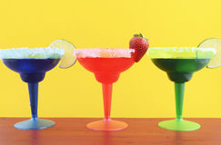 Happy Cinco de Mayo colorful party theme. With bright color margarita drinks on red wood table and yellow background royalty free stock photography