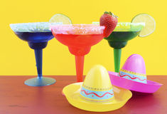Happy Cinco de Mayo colorful party theme. With bright color margarita drinks on red wood table and yellow background