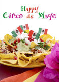 Happy Cinco de Mayo party table. With nachos food platter and bright orange, red, and pink napkins on a red wood background