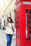 Happy city traveler woman stands next to a red telephone booth n London royalty free stock photography
