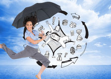 Happy classy businesswoman jumping while holding umbrella Stock Photography