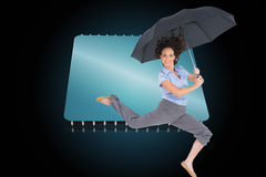 Happy classy businesswoman jumping while holding umbrella. Composite image of happy classy businesswoman jumping while holding umbrella Stock Photos
