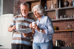 Happy classy couple in their sixties laughing at the kitchen Stock Photos