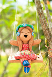 Happy Clay doll playing swing Royalty Free Stock Images