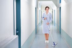 Happy cleaner mopping floor in hospital Royalty Free Stock Photography